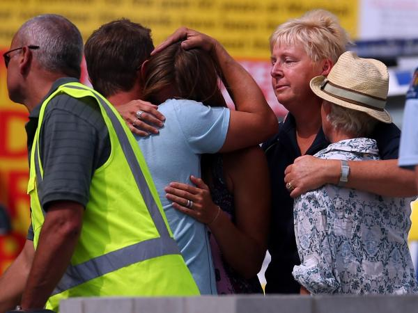 People grieve outside New Zealand's Muriwai Surf Lifesaving Club after the fatal shark attack at Muriwai Beach on Wednesday.