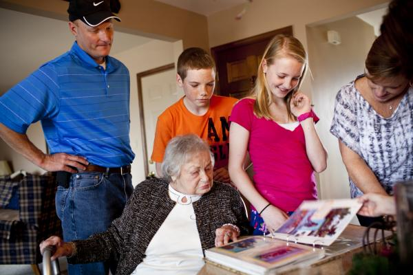 The Martin family (from left) — David; Chris, 14; Lauren, 12; and LaDonna — gather around AnnaBelle as they look through a photo album of a family vacation.