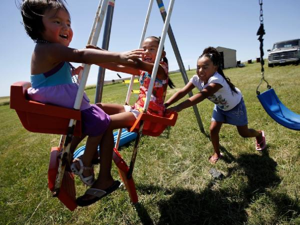 Daylyn, 3, Rashauna, 6, and Antoinette, 8, play on a swing set in their great grandparents' back yard on the Crow Creek Reservation. The children were taken from their mother, by South Dakota's Department of Social Services they spent a year and a half in foster care, despite the fact that she was never arrested or charged with any thing.