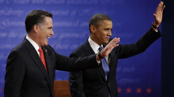 Mitt Romney and President  Obama wave to the audience during the first presidential debate at the University of Denver, on Wednesday.