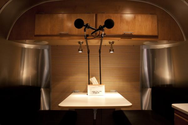 An inside look of the trailer's soundproof recording studio. Below the microphones is a card for the participants' information and a box of tissues.
