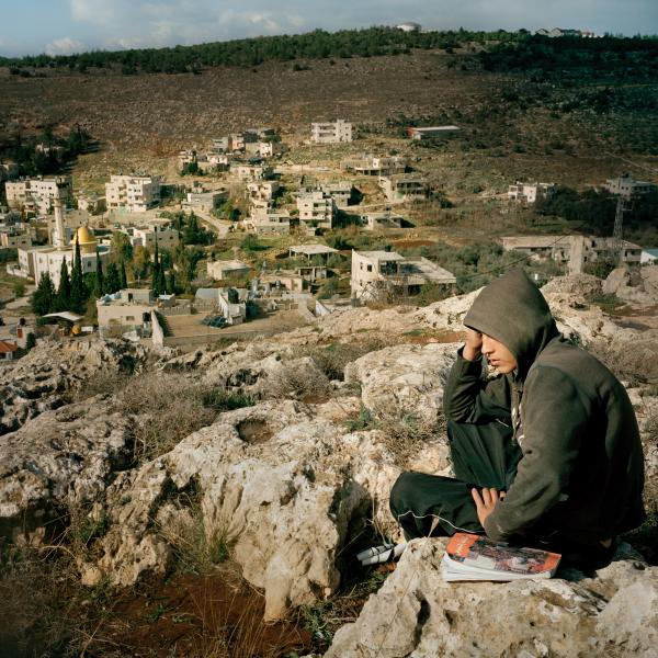 Karim is studying for an exam, near his home at Wadi Fuqin. The youth of the village are very educated and most of them continue to study university in Palestinian territories.