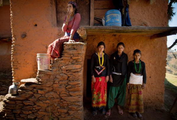 Tulachi, 15, Jandhara, 15, and Amana, 14, pose for a photo in front of the entrance to a crawlspace under their home, which serves as their extended family's <em>chaupadi </em>shelter, in Rima village. They share the space with the household's herd of goats.