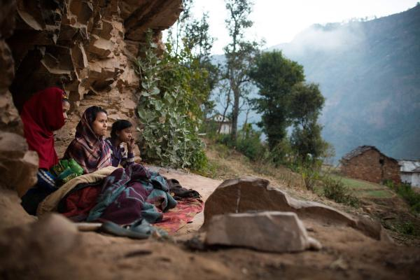 Young women observing <em>chaupadi</em> wake up under a rock outcropping in Kalekanda village, Achham, Nepal.
