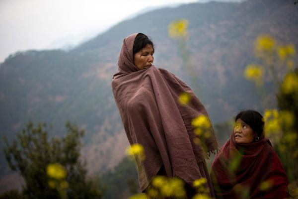 "Sauri (left) and her sister-in-law Birma stand in the spot where Sauri's 17-year-old daughter, Laxmi, recently burned to death while sleeping in a <em>chaupadi</em> shed in an area far from the family's home, near Dhakari village, Achham, Nepal. ""I have many daughters,"" said Sauri, ""but she was the one who was always with me."" The family has since destroyed the shed."