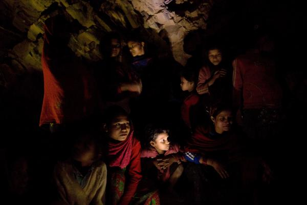 A group of women and girls chat around a fire as they prepare to sleep under a rock outcropping in observance of <em>chaupadi</em> in Kalekanda village. The space, shared by all of the village women, provides no protection from the elements.