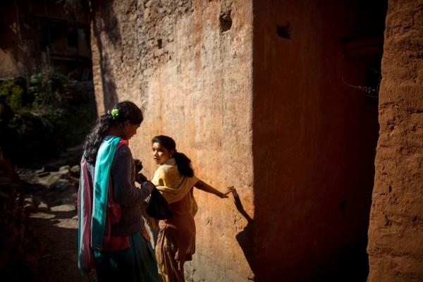 Radhika (left), 14, avoids touching others in her village as she takes a back path toward a water pump where girls practicing <em>chaupadi</em> are allowed to bathe, in Siddheshwar village, Achham, Nepal. During <em>chaupadi</em>, women may not use the regular village water sources, often walking long distances for obligatory daily washing.