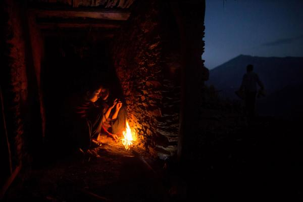 Nabina (left), 17, and Khadi, 12, huddle around a fire for warmth as they prepare to sleep in the household <em>chaupadi</em> shelter, a crawlspace with no door under the home shared with the family's animals.
