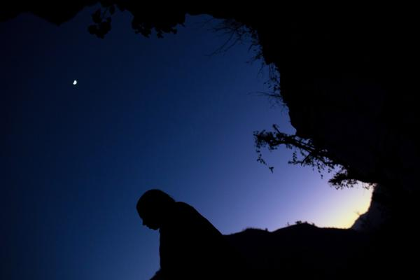 The moon glows overhead as Maisara, 15, prepares to sleep under a rock outcropping in observance of <em>chaupadi</em> in Kalekanda village.