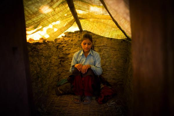 Wearing her school uniform, Jaukala, 14, poses for a photo in the family's <em>chaupadi</em> shelter, a squat shed measuring approximately 1 meter by 2 meters, in Rima village, Achham, Nepal. A tarp serves as a temporary roof to this structure, still under construction. Jaukala must sleep here while she has her period.