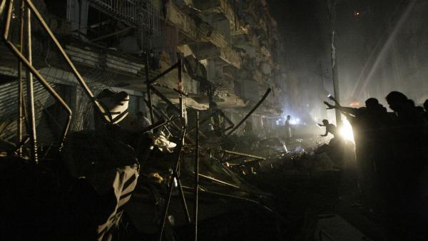 Pakistanis check the site of a bomb blast in Karachi on Sunday. Pakistani officials say the blast has killed dozens of people in a neighborhood dominated by Shiites.