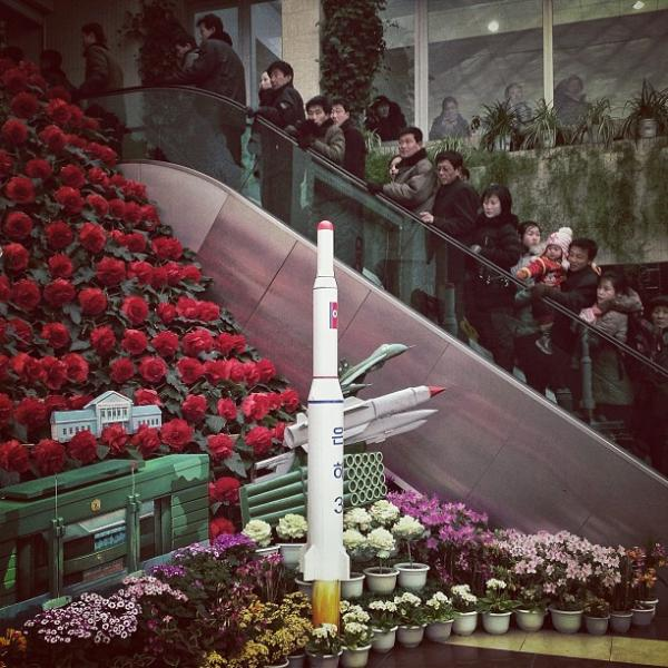 """North Koreans ride an escalator past a model of the country's Unha-3 rocket as they enter an exhibition in #Pyongyang of #Kimjongilia flowers named after the late leader Kim Jong Il."""