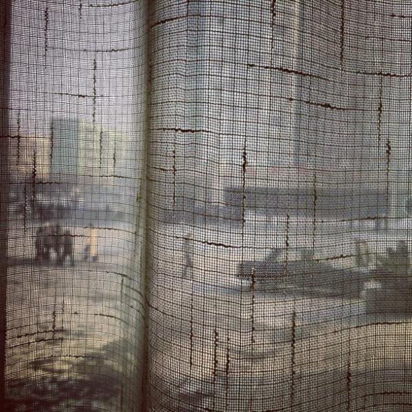 """North Koreans walk along a #Pyongyang street seen through a coffee shop window curtain on January 8, 2013."""