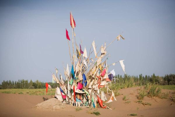 <em>Unrevealed, Site 3 (Harvest Prayers),</em> 2010. Markers for saints in the desert are maintained by <em>shaykhs</em>, who dig out the sands that would otherwise cover them over time. The number of flags on a marker correlates to a saint's power at performing miracles.