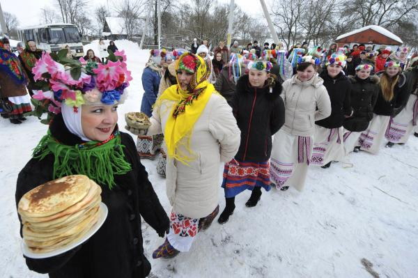 Belarusian women in festive costumes welcome the coming of spring with stacks of blinis during the 2010 Maslenitsa celebrations. The holiday is celebrated in Slavic Orthodox European countries.