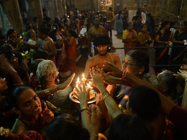 Sri Lankan Hindus receive blessings from a priest holding an oil lamp during the Maha Shivaratri festival at a temple in Colombo on March 10, 2013.