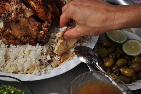 <em>Fatta,</em> a meal of buttery rice served with roasted meat and griddle bread soaked in broth, is often made for guests.