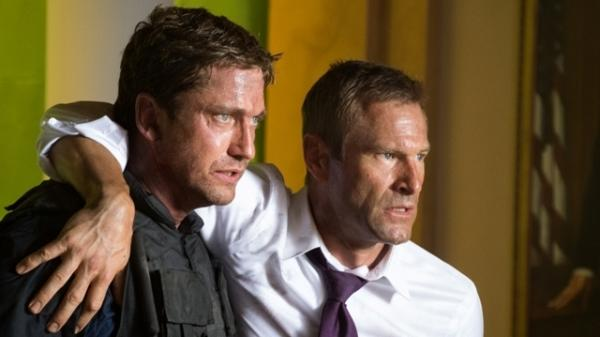 Mike Banning (Gerard Butler) and U.S. President Ben Asher (Aaron Eckhart) flee a destroyed White House in the military-political thriller <em>Olympus Has Fallen</em>.