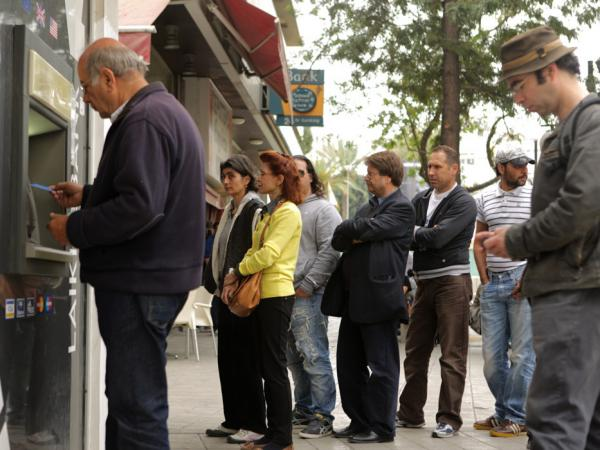 People wait in line to use the ATM at a bank in the Cypriot capital Nicosia.