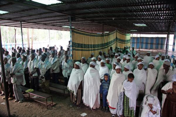 Ethiopian men and women at morning prayer with a traditional dividing curtain between them, Gondar, June 2011.