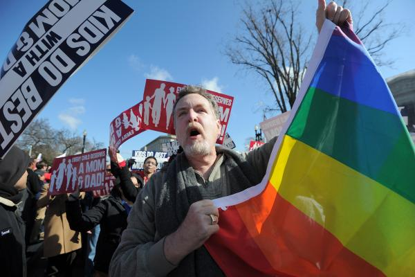 A same-sex marriage supporter holds up a flag among anti-gay protesters in front of the Supreme Court.