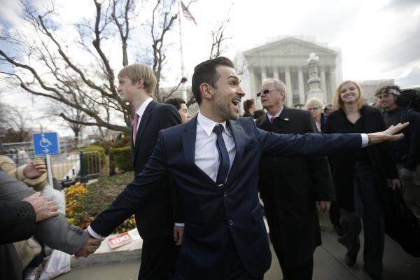 Plaintiff Paul Katami, from Burbank, Calif., waves to supporters as he leaves the Supreme Court in Washington, D.C., on Tuesday, after the court heard arguments on California's ban on same-sex marriage, Proposition 8.
