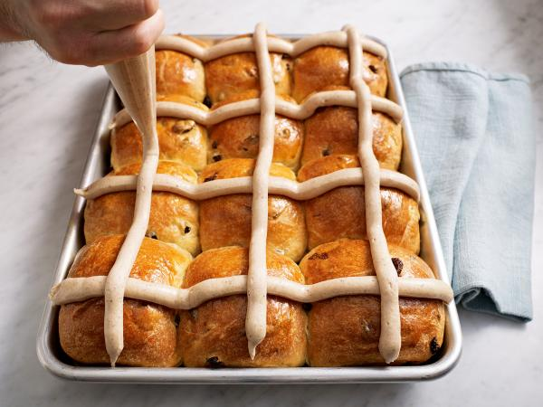 "The <em>Bouchon</em> <em>Bakery<strong></strong></em> cookbook demonstrates how to apply the frosting ""cross"" on a pan of hot cross buns."
