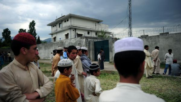 Pakistanis gather in front of the compound where al-Qaida chief Osama bin Laden was killed in Abbottabad. A Western official said five Pakistanis have been detained in  connection with the May 2 raid by U.S. Navy SEALs.