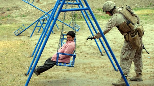 A U.S. Marine pushes a child on a swing in southern Afghanistan on March 4. After a decade of nation-building in Afghanistan, and nearly as long in Iraq, the U.S. appears to be losing it appetite for such efforts.