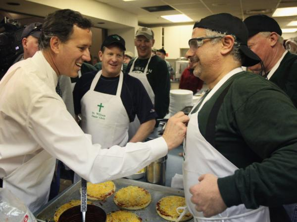 Rick Santorum signs Joe Boulus' apron at a Lenten fish fry Friday in Michigan. Mitt Romney is ahead of Santorum among Catholic voters in the state, despite the fact that Santorum is Catholic.