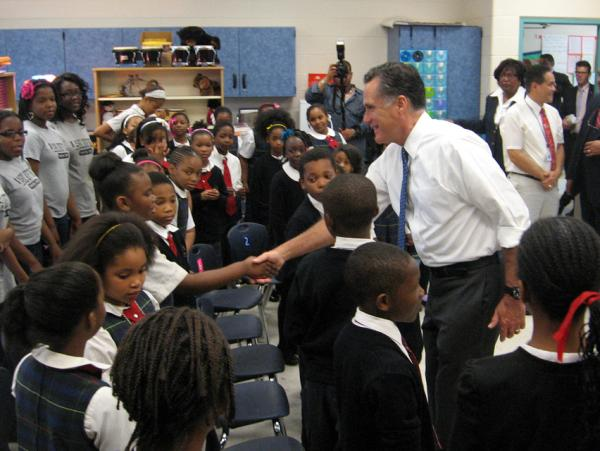Romney greets a student at Universal Bluford Charter School, where he talked about education policy Thursday.