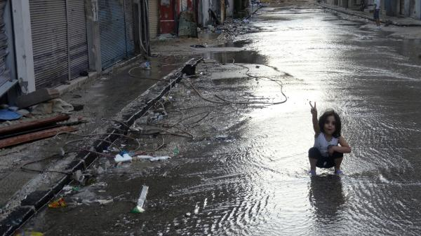 A handout image released by the Syrian opposition's Shaam News Network on Monday shows a girl flashing the sign for victory in a destroyed street flooded with water in the restive central city of Homs.
