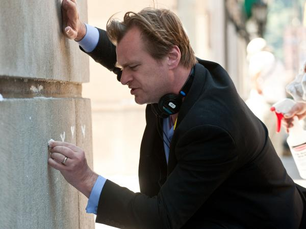 Christopher Nolan on the set of <em>The Dark Knight Rises</em>,<em> </em>drawing some Batman graffiti.