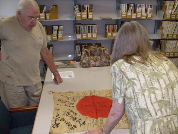 "George Koller (left) shows the ""good luck flag"" to historian Priscilla Wegars of Moscow, Idaho."