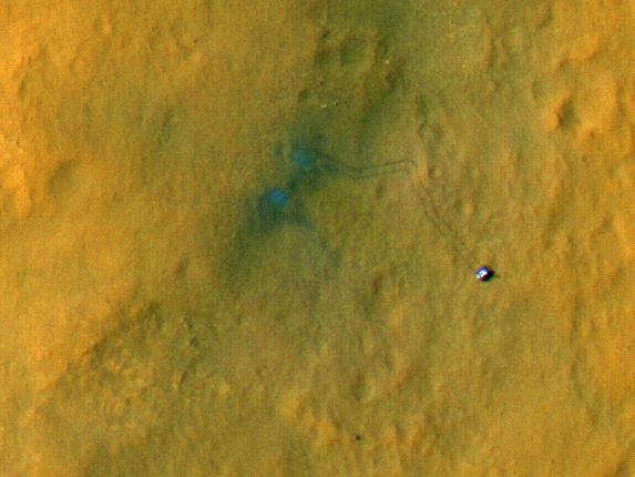Curiosity from above. It's the small object to the right. The rover's tracks extend up and back to the left.