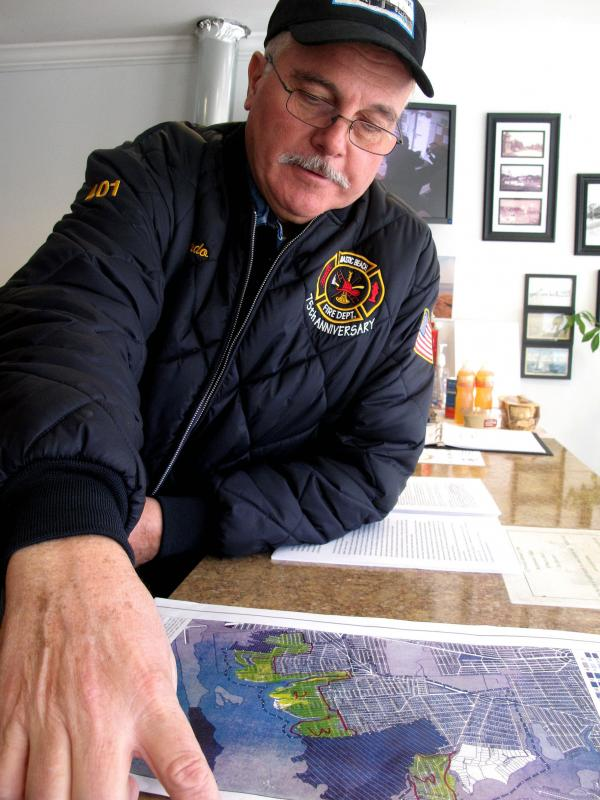 Mastic Beach Mayor Bill Biondi looks over a map of the flooding in his community from Hurricane Sandy. More than 1,000 homes here were inundated with seawater.