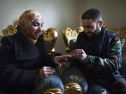 Yusef puts a wedding ring on his fiancee Ghada's finger in the war-torn city of Aleppo in northern Syria on Jan. 17. They met on Facebook and were wed by a rebel commander.