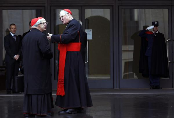 U.S. Cardinal Timothy Dolan (right) chats with other cardinals as they arrive for a meeting at the Synod Hall in the Vatican on Thursday.