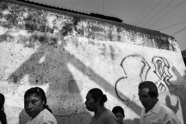 A Holy Week procession passes by walls marked with graffiti of the gang that dominates the zone in Jocotenango, Guatemala, 2001.