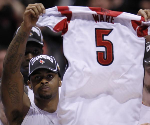 Louisville Cardinals forward Chane Behanan holds up the jersey of injured teammate Kevin Ware after the team's win Sunday over the Duke Blue Devils. Ware broke his leg during the game.