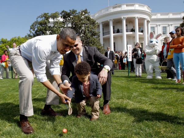 President Barack Obama helps a young participant roll an egg during the White House Easter Egg Roll on the South Lawn of the White House on April 9, 2012 in Washington, DC.