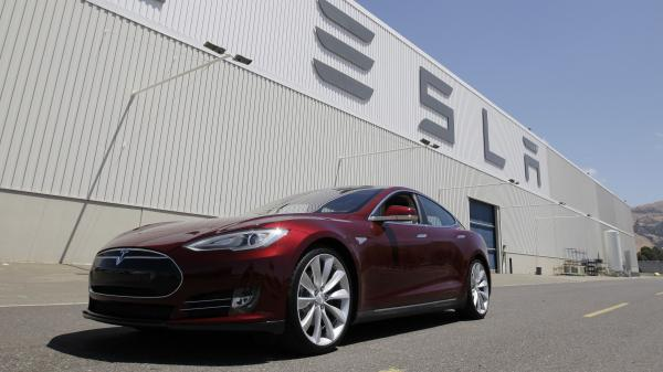 A Tesla Model S drives outside the Tesla factory in Fremont, Calif., on June 22. The electric car was named Automobile of the Year by <em>Automobile</em> <em>Magazine</em> and Car of the Year by <em>Motor Trend</em>.
