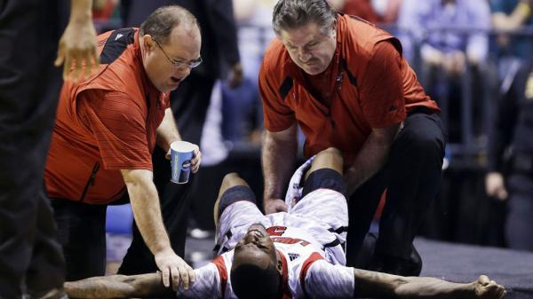 Trainers check on Louisville guard Kevin Ware after he injured his lower right leg during the Midwest Regional final against Duke in the NCAA college basketball tournament.