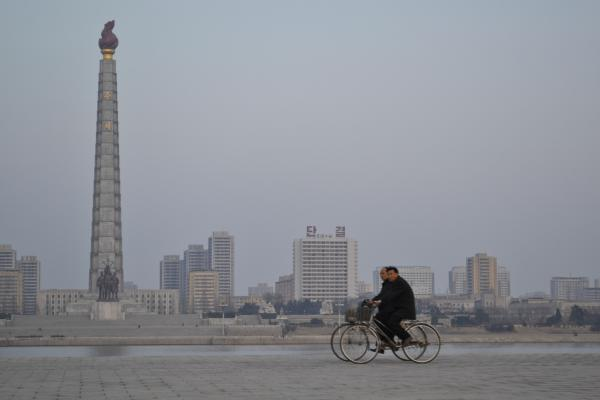 Men bicycle in front of the tower of Juche Ideal.