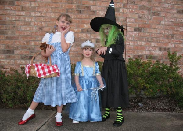 """Halloween 2009, Houston — there's Kathryn as Dorothy with her little moose named Toto (we didn't have a stuffed dog) and 2-year-old Eliza as a very tiny Good Witch Glinda, plus Phoebe as the Wickedest Witch of the West. The gorgeous costumes were handmade by my mother-in-law."" — Brenda Lightfoot"