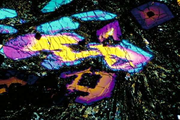 A slice of a meteorite from the moon produces dazzling colors when passed in front of a polarized filter. Researchers use the colors to identify minerals in the rock and match it to samples brought back by the Apollo missions.