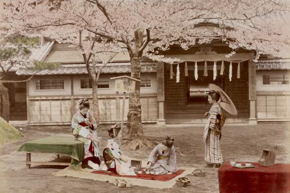 Women in the shade by a traditional Japanese building.