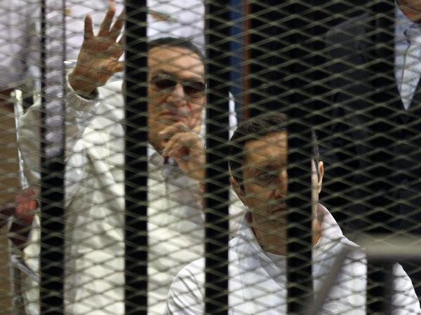 Ousted Egyptian President Hosni Mubarak, waves from behind his son, Alaa, during the opening session of Mubarak's retrial in Cairo on Saturday.