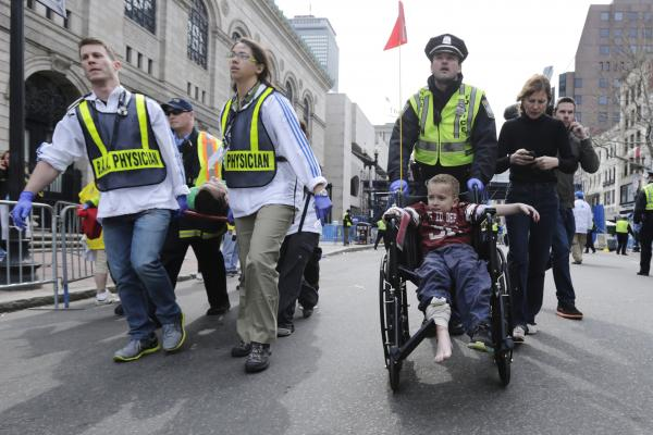 A Boston police officer wheels an injured boy down Boylston Street as medical workers carry an injured runner.