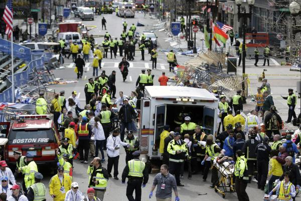 Medical workers aid injured people at the finish line. The cause of the explosions has not been determined.